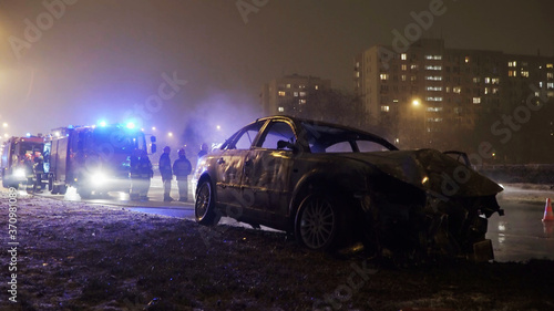 Photo Winter car accident, burned car with fire engine and buildings in the background
