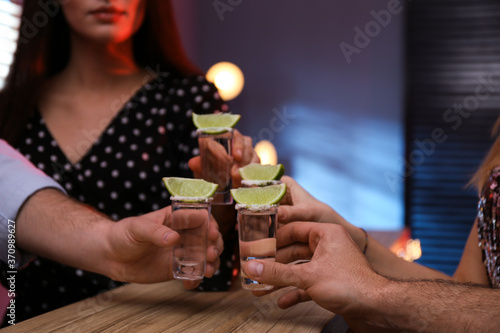 Canvas Print Young people toasting with Mexican Tequila shots at bar, closeup