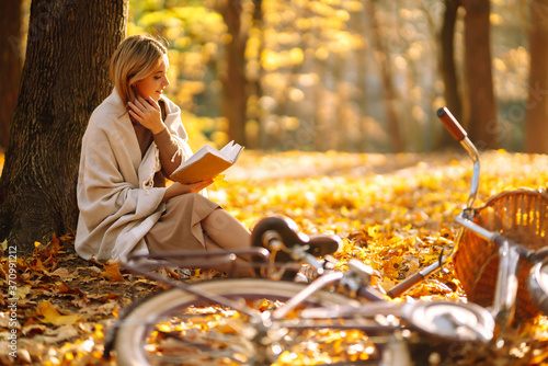 Fototapeta Stylish woman reading a book in the autumn park. Relaxation, enjoying, solitude with nature. obraz