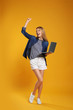 Full length portrait of emotional woman with modern laptop on yellow background