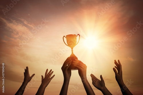 Obraz na płótnie Winning team with gold trophy cup against shining sun in sky