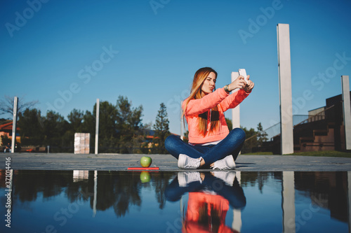 Gorgeous young woman making self portrait while holding up her smart phone, beau Canvas Print