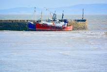 Two Coloured Fishing Boats Are Moored Alongside Barry's Old Harbour Wall As The Tide Comes In.  The Old Harbour Is A Safe Haven For Boats Needing Shelter.