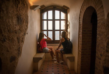 Two Women Sitting By A Window Looking At The Landscape. Rear View Of Two Pretty Young Women Sitting By A 15th Century Window Of A Medieval Castle. Tourism During The Pandemic.