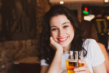 Happy Young Beautiful Woman Toasting With You With A Glass Of Cold Beer In A Pub