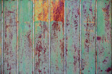 Old rusty metal fence. Green paint will peel off the fence. Close-up. background. copy space