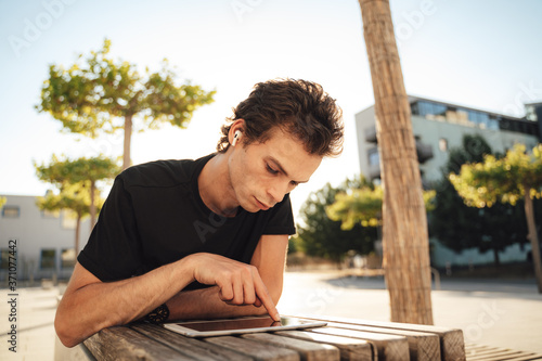 Foto Young male university student touching screen of digital tablet while lying on b