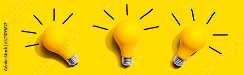 Fototapeta Three yellow light bulbs - flat lay from above