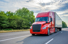 Red Big Rig Long Haul Semi Truck With Black Grille Transporting Cargo In Dry Van Semi Trailer Running On The Wide Highway Road