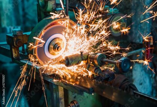 Obraz na płótnie Hot sparks at grinding steel material - Sparks of welding.