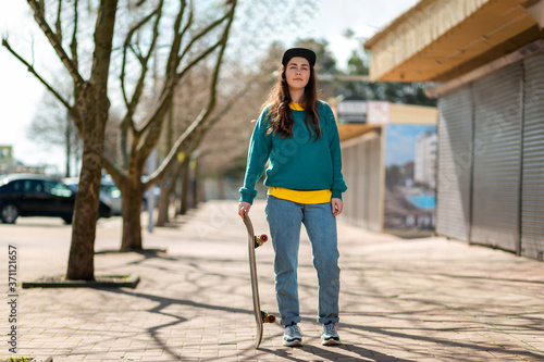 A young Caucasian hipster woman stands leaning on a skateboard Canvas-taulu