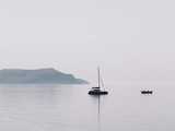 Minimal view of the sea, Crimea. Morning seascape with a lonely boat floating in the middle of the sea and overlooking the mountains in the haze. Minimalism. - 371149621