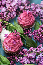 Two Pink Cupcakes Among Purple Lilac On Blue Table