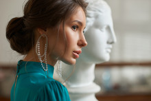 Closeup Half Face Portrait Of Elegant Woman In Green Dress Wearing Earrings Against White Sculpture In Art Class Or Studio. Beautiful Fashion Female Model With Perfect Natural Makeup