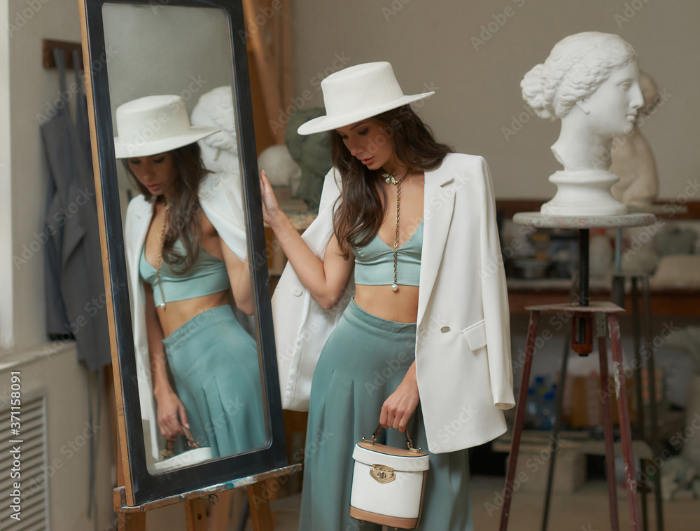 Fototapeta Pretty slim caucsian tanned woman in green top, palazzo trousers, white hat and oversize blazer, holding handbag standing with head down near mrirror in art studio between sculptures