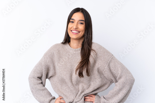 Fototapeta Young brunette woman over isolated white background posing with arms at hip and smiling obraz
