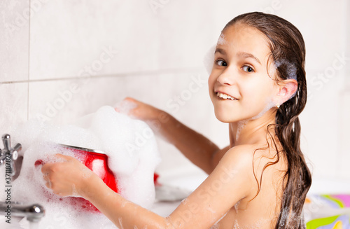 Cheerful little caucasian girl plays with foam while bathing in the bathtub during quarantine Fotobehang