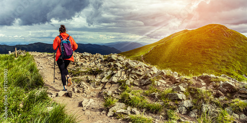 Girl hiking in mountains at sunset Fototapete