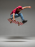 Cool young guy skateboarder jumps on skateboard in studio on grey background. Photography about skateboarding tricks