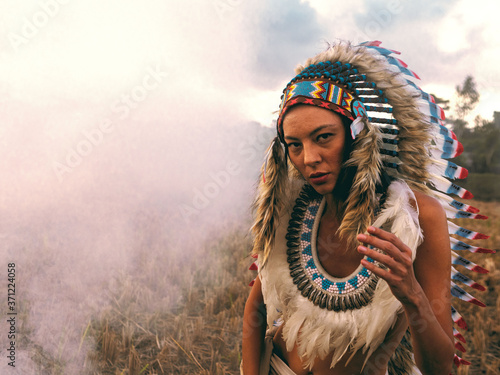 Fotomural Young woman dressed as a North American Indian in a field