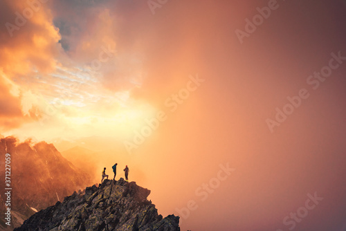 Together overcoming obstacles as a group of three people up on the top of a mountain фототапет