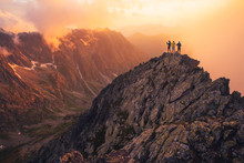 Together Overcoming Obstacles As A Group Of Three People Raising Hands Up On The Top Of A Mountain. Celebrate Victory And Success Over Sunset Background. Goal Achievement Symbol..