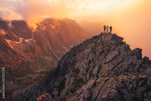 Fototapeta Together overcoming obstacles as a group of three people raising hands up on the top of a mountain. Celebrate victory and success over sunset background. Goal achievement symbol.. obraz