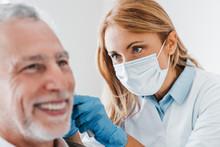 Doctor Checking Ear Of Elderly...