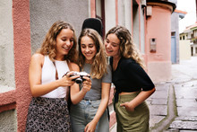 Group Of Pleasant Women Watching Pictures From Photo Camera In S