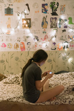 Girl Watching A Movie On The Phone On The Bed In The Lamp Light