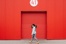Young Asian Man Walking, Red Background