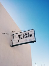 """A Sign That Says """"""""You Live. You Learn"""""""""""