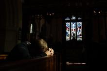 Man Bows His Head In Prayer In Church.