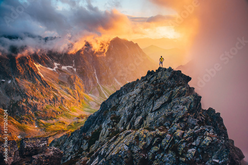 Fotografia Man on the top of the hill watching wonderful scenery in mountains during summer colorful sunset in High Tatras in Slovakia