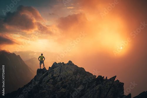 Fotografie, Obraz Hiker on the top of the hill looking at beautiful sunset sky