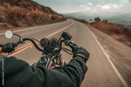 Obraz na plátně A first person point of view angle riding on the back from a motor cycle rider riding on an empty road on a sunny day with a red bike