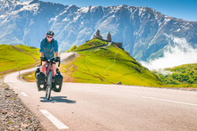 Cyclist On The Road In Scenic Caucasus Nature With Gergeti Trinity Monastery In The Background. Traveller On Bicycle,