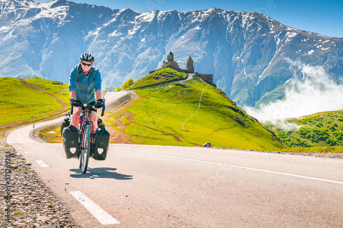 Cyclist on the road in scenic caucasus nature with Gergeti trinity monastery in the background Fototapeta