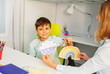Little boy during aba development therapy sitting selecting between two cards of rainbow and storm