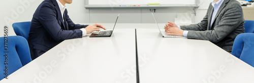Cuadros en Lienzo デスクを挟んで対面し、パソコンを使ってミーティングをする2人のビジネスマン