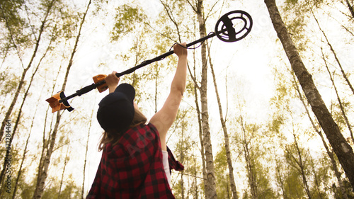 Treasure hunter, young woman holding metal detector in the air in the forest Fototapet