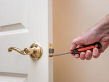 Carpenter Repairing Door Latch. Handyman Using Screwdriver To Install Door Lock Hardware.