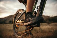 Crop Man Riding Bike In Field