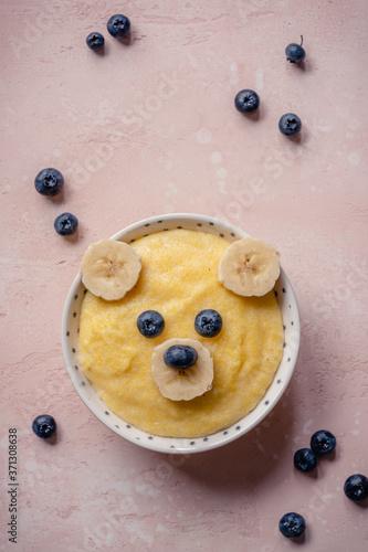 Obraz Kids breakfast, porridge with fruits and berries, face bears - fototapety do salonu