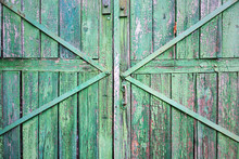 Wooden Background. Detail Of Old Wooden Gates, Doors With Cracked Paint, Metal Lock, Reinforced With Strips Of Metal.