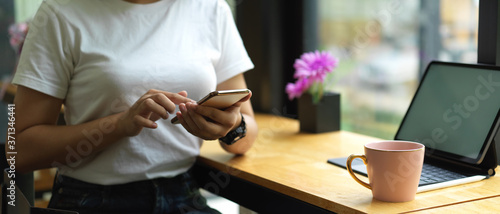 Photo Female using smartphone while sitting at worktable with mock up tablet