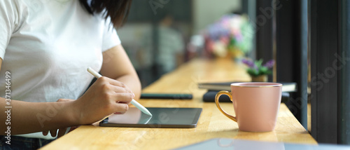 Side view of female hand using digital tablet on wooden bar in cafe Fototapet