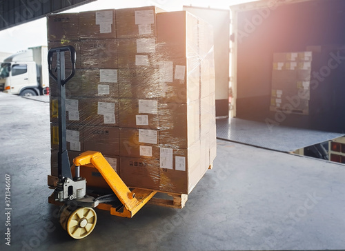 Shipment, Cargo freight, Delivery. Logistics and transportation. Hand pallet truck with pallet goods loading into container truck.