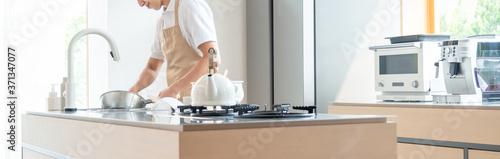 Leinwand Poster キッチンで料理する若い男性