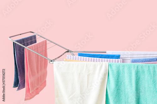 Obraz na plátně Clean clothes hanging on dryer against color background